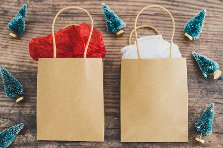 shopping bag with miniature Christmas trees around it ,concept of festive season gift purchases and shopping