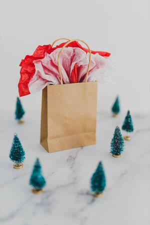 shopping bag with miniature Christmas trees around it on white,concept of festive season gift purchases and shopping