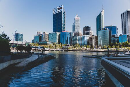 PERTH, WESTERN AUSTRALIA - December 24th, 2019: Perth city skyline from Elizabeth Quay with contrasty tones and strong summer sunshine reflecting on the modern skyscrapers and architecture of the CBD