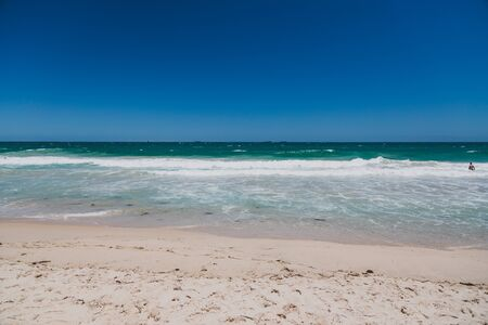 PERTH, WESTERN AUSTRALIA - December 27th, 2019: detail of Scarborough beach, one of the most popular beaches near Perth on the Indian Ocean, with intense turquoise water and blue sky with strong sunshine, with ships in the distance Editorial