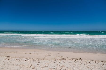 view of Scarborough beach, one of the most popular beaches near Perth on the Indian Ocean, with intense turquoise water and blue sky with strong sunshine, with ships in the distance