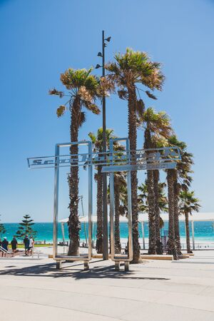 PERTH, WESTERN AUSTRALIA - December 31st, 2019: view of Scarborough beach near Perth and its iconic sign with palm trees on a sunny and warm summer day