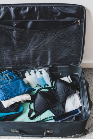 travel essentials and packing for a holiday concept, luggage with pile of clothes beach towel and bikini next to transparent liquid bag for airport security screening compliance