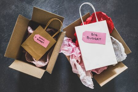 big vs small budget conceptual still-life, different size shopping bags with text on price tags on top of delivery parcels