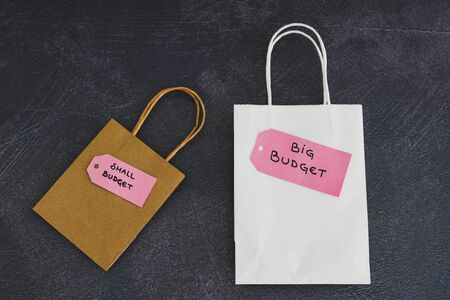 big vs small budget conceptual still-life, different size shopping bags with text on price tags