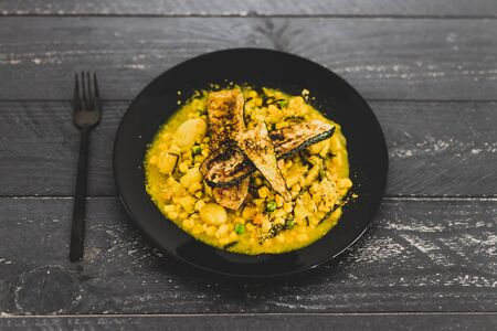 healthy plant-based recipes concept, grilled zucchini with curried rice with peas and carrots Stock Photo