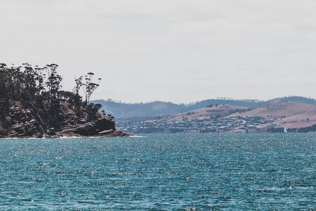 Tasmanian coastline and Derwent river waterside seen from a beach near Hobart on a cloudy day