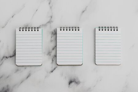 business lifestyle and productivity conceptual still-life, minimalist image of three blank notepads lined up on marble desk with desaturated tones Stock Photo