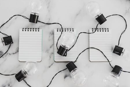 brainstorming and finding innovative ideas for your business conceptual still-life, group of notepads with string of light bulbs on them