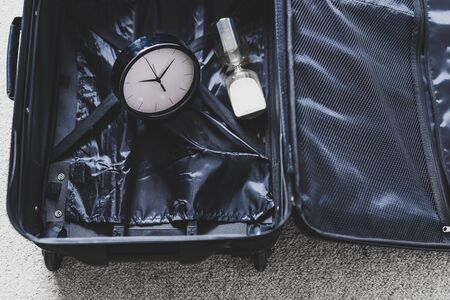 time to travel or delay during a trip conceptual still-life, empty suitcase with clock and hourglass in it Stockfoto