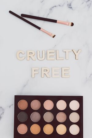 beauty industry and vegan products conceptual still-life, make-up brushes and eyeshadow palette with Cruelty free text next to them referring to the use of synthetic bristle and items not tested on animals Standard-Bild
