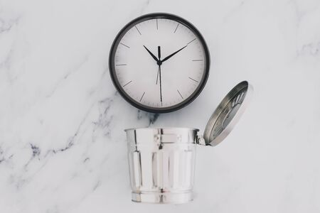 concept of not wasting time and productivity, clock next to semi-open mini garbage bin on desk Stock Photo - 140019154