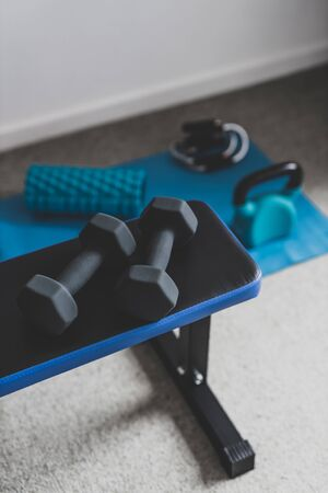 home gym and fit lifestyle still-life, room with flat bencha nd dummbells surrounded by other fitness equipment like yoga mat with kettlebell and jumpying rop shot at shallo depth of field Stock Photo - 140019168
