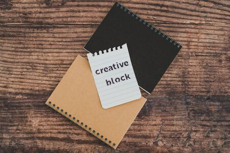 creative block or writer's block conceptual still-life, notepads on wooden desk with text doodle on piece of paper Stock Photo - 140019184