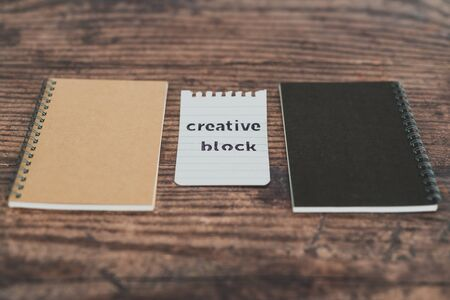 creative block or writer's block conceptual still-life, notepads on wooden desk with text doodle on piece of paper Stock Photo - 140019188