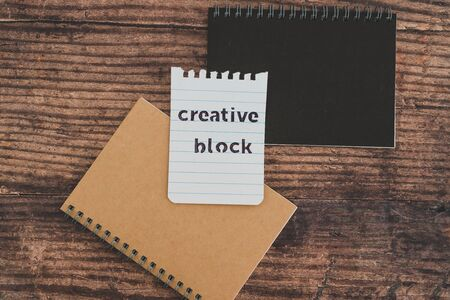 creative block or writer's block conceptual still-life, notepads on wooden desk with text doodle on piece of paper Stock Photo - 140019190
