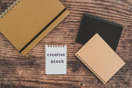 creative block or writer's block conceptual still-life, notepads on wooden desk with text doodle on piece of paper