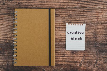 creative block or writer's block conceptual still-life, notepads on wooden desk with text doodle on piece of paper Stock Photo - 140019194