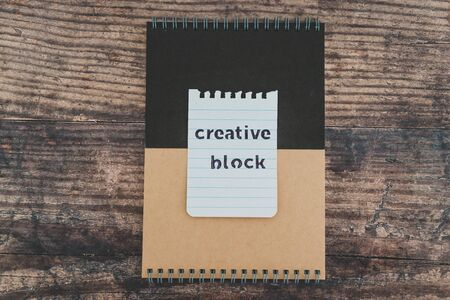 creative block or writers block conceptual still-life, notepads on wooden desk with text doodle on piece of paper Stock Photo
