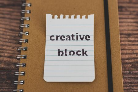 creative block or writer's block conceptual still-life, notepads on wooden desk with text doodle on piece of paper Stock Photo - 140019213