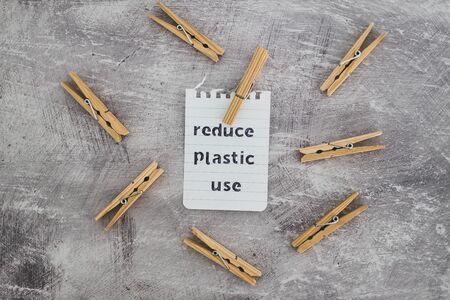sustainable living conceptual still-life, Reduce plastic use message with wooden pegs to hang the washing Stock Photo - 140077797