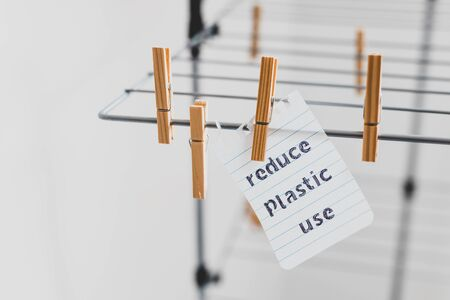 sustainable living conceptual still-life, Reduce plastic use message on wooden peg on clothes airer Stock Photo - 140077865