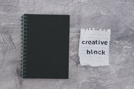 lack of inspiration or motivation conceptual still-life, scrunched paper with Creative Block text on desk with notepad Stock Photo