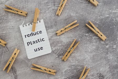 sustainable living conceptual still-life, Reduce plastic use message with wooden pegs to hang the washing  Stock Photo