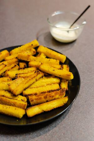 healthy plant-based snack recipes concept, homemade vegan polenta chips made with oat milk and cornmeal with vegan aioli sauce to the side Stock Photo