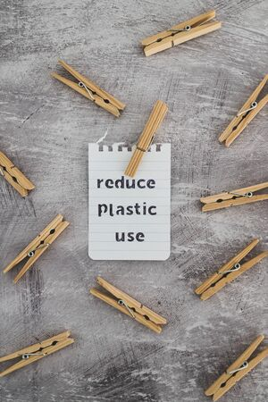 sustainable living conceptual still-life, Reduce plastic use message with wooden pegs to hang the washing