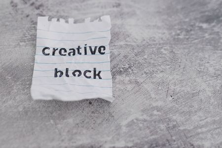lack of inspiration or motivation conceptual still-life, scrunched paper with Creative Block text on desk