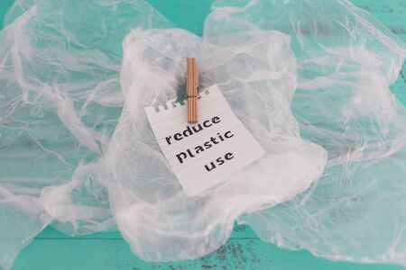 sustainable living conceptual still-life, Reduce plastic use message with wooden peg on top of plastic bags