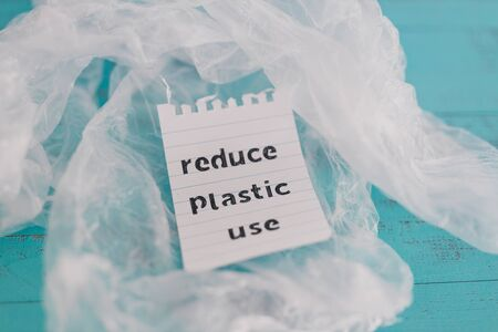 sustainable living conceptual still-life, Reduce plastic use message on top of a bunch of plastic bags Stock Photo - 140077968