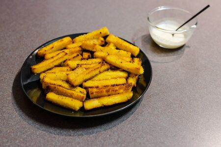 healthy plant-based snack recipes concept, homemade vegan polenta chips made with oat milk and cornmeal with vegan aioli sauce to the side Stock Photo - 140078126