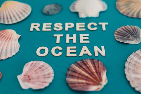 respect for the planet conceptual still-life, respect the ocean text surrounded by colorful shells on blue background Stock Photo
