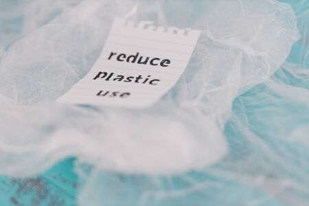 sustainable living conceptual still-life, Reduce plastic use message on top of a bunch of plastic bags Stock Photo