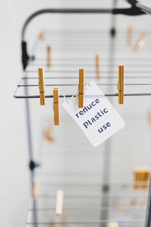 sustainable living conceptual still-life, Reduce plastic use message on wooden peg on clothes airer