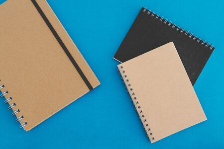 group of minimalist looking notebooks of different shapes and colour isolated on blue background Stock Photo
