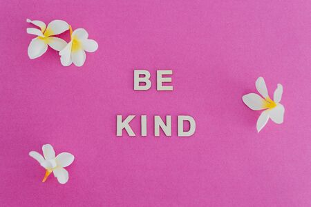 Be Kind message on pink background surrounded by flowers, concept of good behaviours for a better society