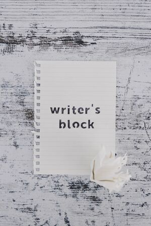 creative block or lack of inspiration conceptual still-life, piece of paper on wooden desk with Writers Block text with scrunched paper ball next to it