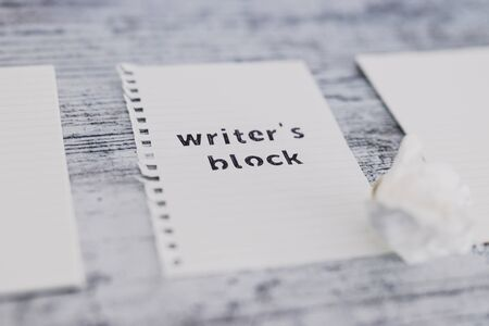 creative block or lack of inspiration conceptual still-life, piece of paper on wooden desk with Writers Block text surrounded by blank notepads and with scrunched paper ball next to it