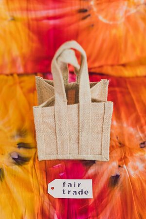 ethical shopping and locally sourced items conceptual still-life, small canvas bag made of natural materials with Fair Trade text on price tag on hippie tie dye background