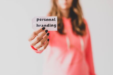 concept of influencers and fame, girl holding Personal Branding message on price tag close to the camera shot at shallow depth of field Stock fotó