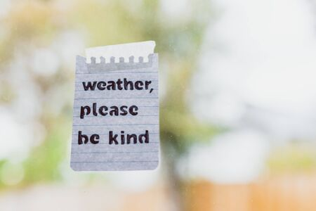 weather events and climate change conceptual still-life, Weather please be kind message with sticky tape on window glass with bokeh on stormy weather and grey sky over a backyard