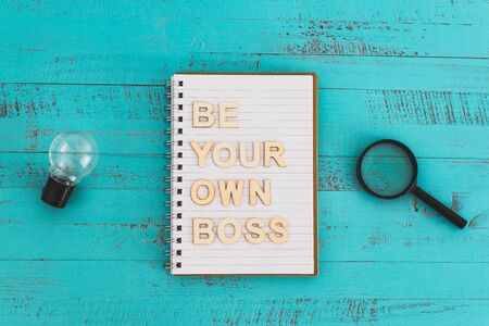 working for yourself and being a business owner conceptual still-life, notebook on desk with Be your own boss text surrounded by lightbulbs symbol of good ideas