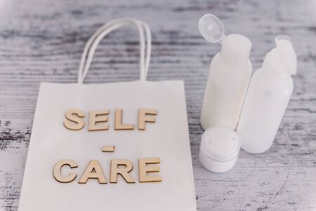 self-care message on shopping bag surrounded by skincare products, concept of beauty industry and spa treaments