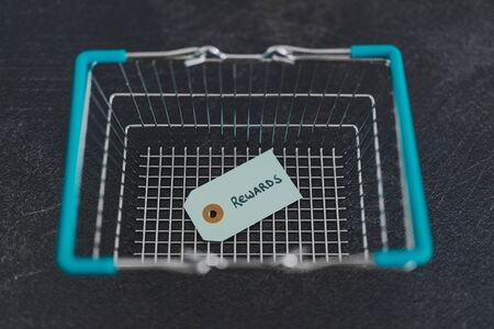 customer rewards and fidelization incentives conceptual still-life, shopping basket with price tag with Rewards written on it