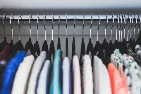 organizing and tidying up conceptual still-life, wardrobe with tidy selection of different knits lined up on black flocked hangers shot at shallow depth of field