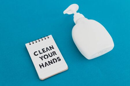 keep your hands clean to fight bacteria and viruses conceptual still-life, liquid soap next to memo with Clean your Hands text on blue background Banco de Imagens