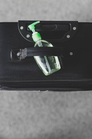 travel safety and hygiene in times of virus outbreak, packing a suitcase with hand sanitizer bottle on top of it